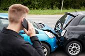 Young Male Motorist Involved In Car Accident Calling Insurance Company Or Recovery Service poster