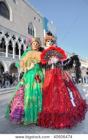 VENICE - MARCH 04: Two participants wear colorful dresses, masks and hats on St. Mark's square during famous traditional Venetian carnival taking place every year in Venice, Italy on March 04, 2011.