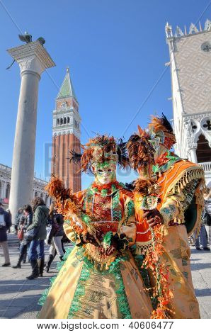 VENICE - MARCH 04: Two participants wear colorful costumes, masks and hats on St. Mark's square during famous traditional Venetian carnival taking place every year in Venice, Italy on March 04, 2011.