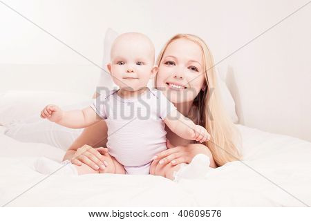 happy young mother and her one year old daughter in bed at home