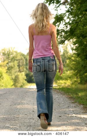 Slender Blond Walking On Gravel Road