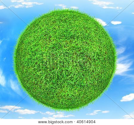 World globe as green grass planet with blue sky background.