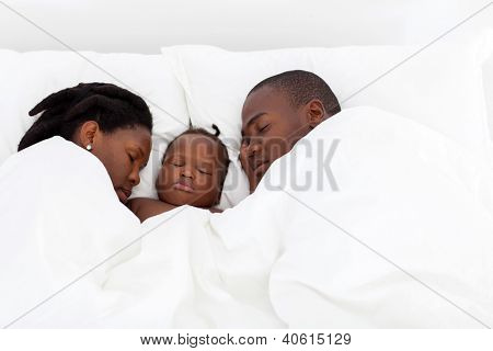 african american family sleeping on bed