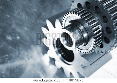 large titanium gears, cogwheels, set against a brushed steel background, engineering parts in blue toning