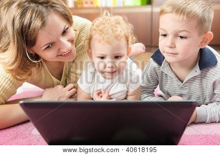 Young Mother With Her Son And Daughter On Floor