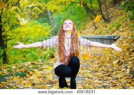Redhead Girl Throwing Leaves In Autumn Park