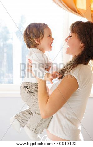Mother Holding Little Son Against Window