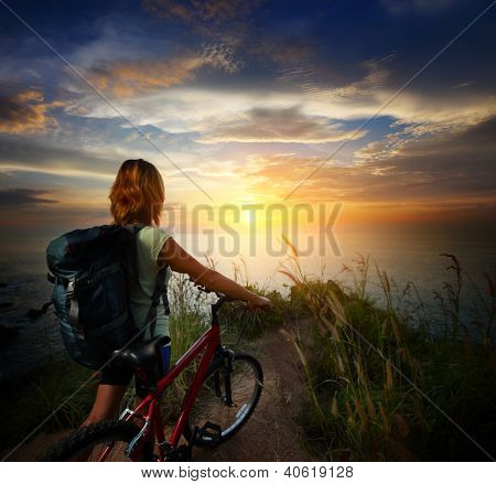 Young woman with backpack standing on ground near her bicycle and enjoying sunset over sea