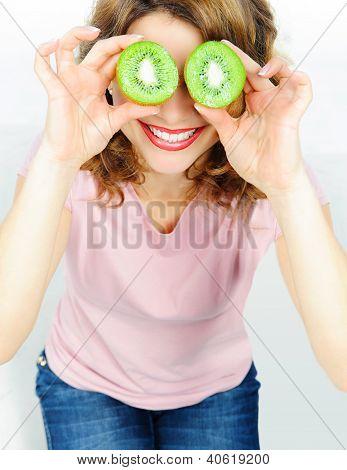 Funny woman holding kiwis fruit for her eyes