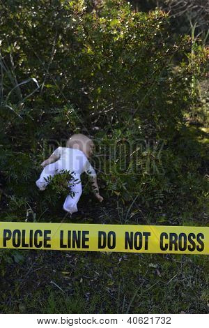 Crime scene in the forest: Yellow police line do not cross tape and doll