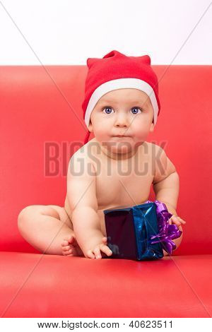 Little Cute Boy Dressed In Santa Clause Hood Sitting On Sofa