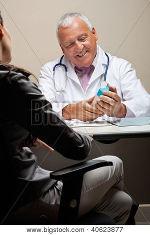 Senior male doctor holding medicine box while female patient sitting on chair