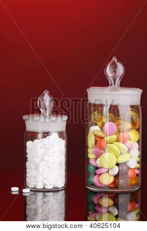 Capsules and pills in receptacles on red background