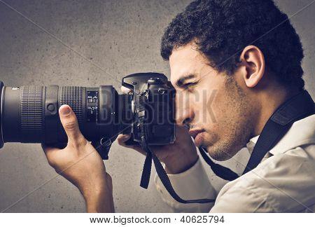 Hombre mulato usando una cámara profesional