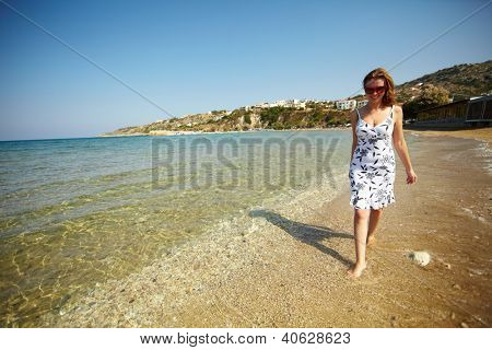 Young woman walking in water by the coastline