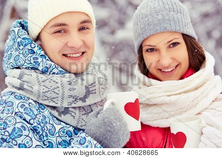 Portrait of happy young couple holding cups with red hearts and looking at camera