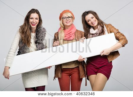 Three smiling women with empty board