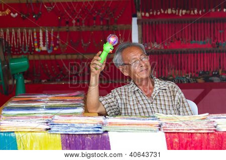 KHAO LAK, THAILAND - NOV 05: Unidentified old man selling clothes on the local market in Khao Lak. This market is also tourist attraction in Phang Nga province, Thailand on Nov.05, 2012.