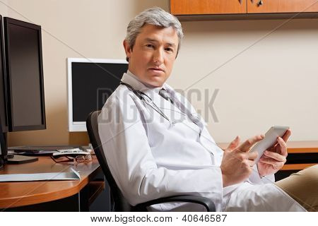 Portrait of serious mature male doctor holding digital tablet while sitting by desk