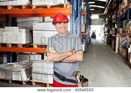 Portrait of happy mid adult foreman with arms crossed at warehouse