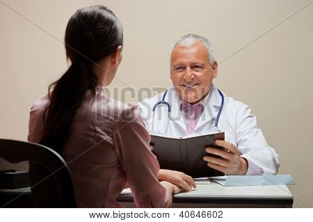 Senior male doctor with book smiling while looking at patient