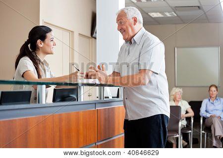 Senior Man Kommunikation mit weiblichen Empfangsdame während Frauen sitzen im Hintergrund