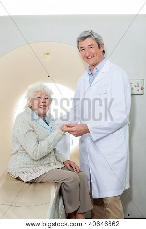 Portrait of happy male doctor with female patient sitting on CT scan machine