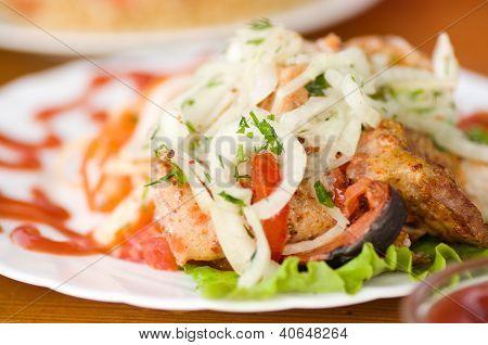 Appetizing weal kebab on skewers with greens