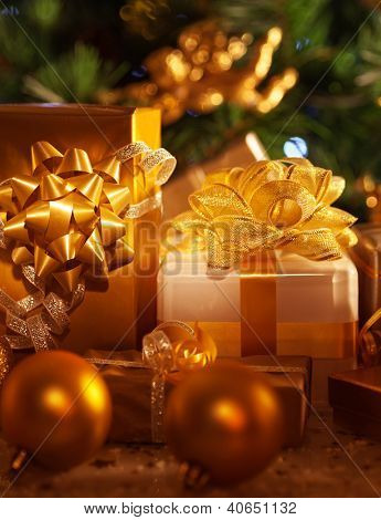 Image of golden gift boxes lying down under festive spruce tree, luxury presents, New Year party, wintertime home ornament, Christmas tree, beautiful shiny decorations, traditional celebration