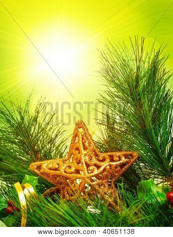 Picture of Christmastime decorative border, branch of Christmas tree decorated with golden star and ribbon, green pine tree twig isolated on yellow sunlight background, New Year holiday greeting card