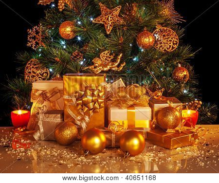 Picture of many golden presents boxes under luxury Christmas tree, beautiful adorned New Year spruce, shiny xmas decoration, holiday gifts, Christmastime party, festive ornament, yellow candle light