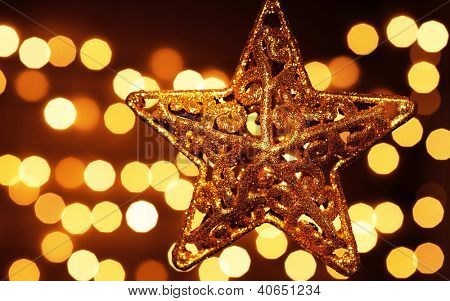 Image of beautiful golden star decoration isolated on festive blur lights background, Christmas eve, New Year night, holiday ornament, magic illumination, decorative garland, abstract backdrop