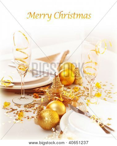 Photo of xmas holiday table setting, closeup festive dinnerware still life, two glasses for champagne, traditional New Year alcohol beverage, luxury white plate decorated with golden bubble toy