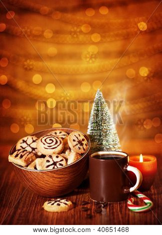 Image of Xmas sweets, traditional Christmastime gingerbread with candy cane on festive table, coffee cup decorated with little decorative Christmas tree, tasty homemade cookies, New Year eve
