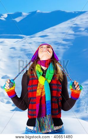 Photo of happy woman having fun outdoors in wintertime, cute teenager looking up in blue sky, beautiful model wearing colorful stylish warm hat, scarf and gloves, winter holiday in snowy mountains