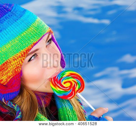 Photo of pretty girl eating sugar candy outdoor in wintertime, closeup portrait of beautiful female wearing warm colorful hat and licking lollipop, christmas sweets, sweet food, winter vacation