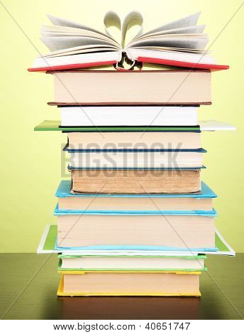 Stack of interesting books and magazines on wooden table on green background