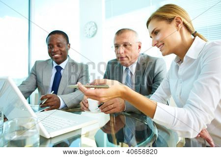 Portrait of pretty secretary pointing at laptop screen while explaining something to her boss and colleague
