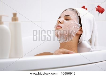 Image of serene woman with facial mask enjoying bath in spa salon
