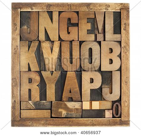 random letters of alphabet and punctuation symbols - vintage letterpress wood type blocks in rustic box isolated on white