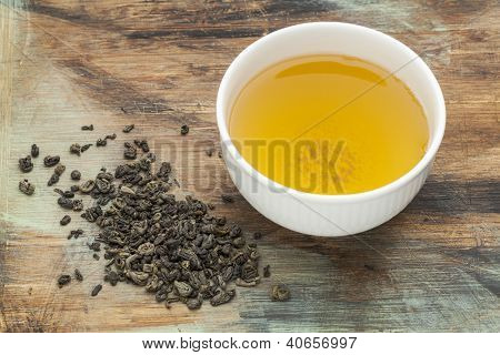 gunpowder green tea - a white cup of drink and loose leaves on a grunge painted wood background