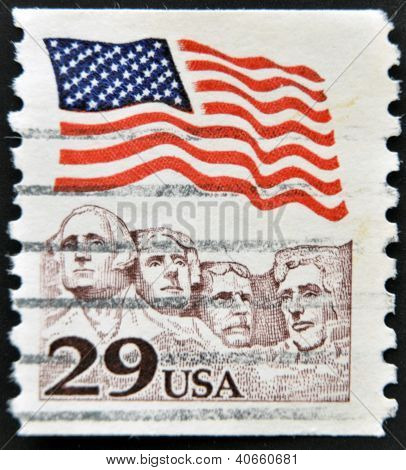 A stamp printed in the USA shows American flag waving above Mt. Rushmore circa 1991