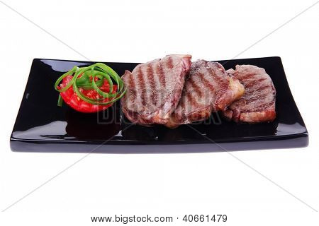 roast meat beef fillet strips on black plate isolated over white background