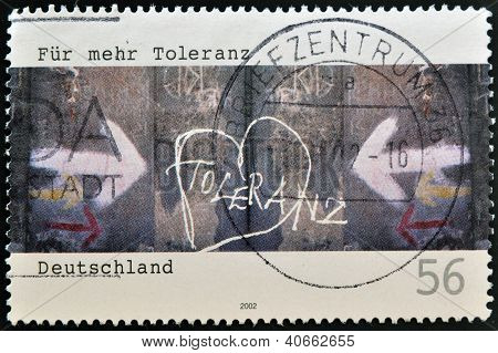 A stamp printed in Germany shows wall painted with the word tolerance circa 2002