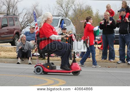 BROKEN ARROW, OK-DECEMBER 8: Unidentified woman in a wheelchair decorated in patriotic colors drives ahead of the Broken Arrow Christmas Parade on December 8, 2012.