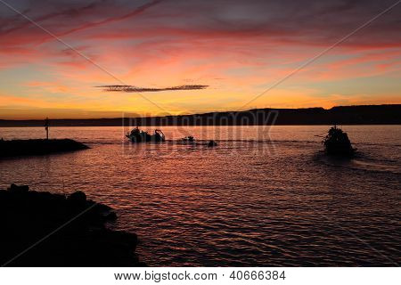Fishing Boats Leaving The Harbor at sunset