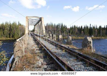 Following a railway track into a bridge above a river.