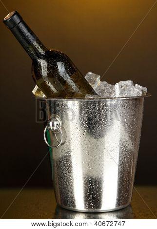 Bottle of wine in ice bucket on darck yellow background