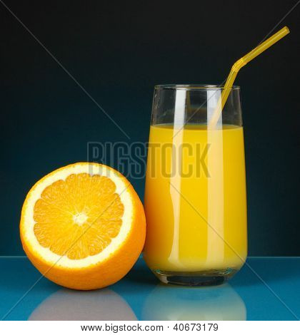 Delicious orange juice in glass and orange next to it on dark blue background