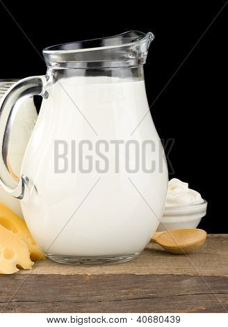 milk products and cheese on wood isolated at black
